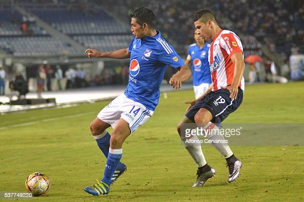 David Silva of Millonarios covers the ball from Alexis Perez of Junior during a first leg match between Junior and Millonarios as part of quarter...