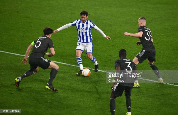 David Silva of Real Sociedad surrounded by Harry Maguire of Manchester United , Eric Bailly of Manchester United and Scott McTominay of Manchester...