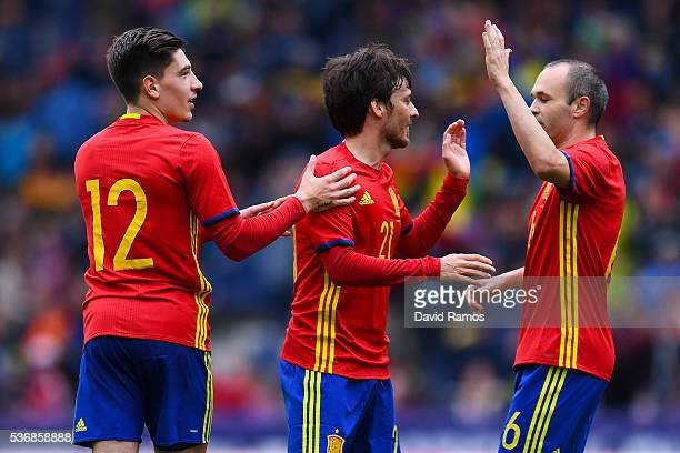 David Silva of Spain celebrates with his teammates Hector Bellerin and Andres Iniesta after scoring the opening goal during an international friendly...