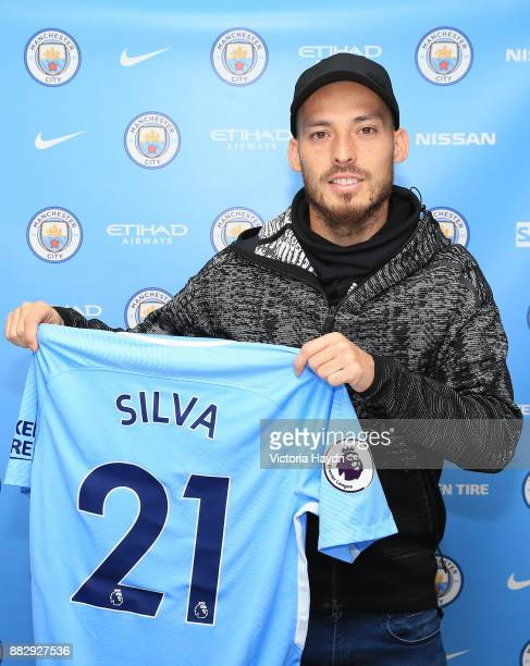 David Silva poses with a shirt as he signs a new contract at Manchester City Football Academy on November 30 2017 in Manchester England