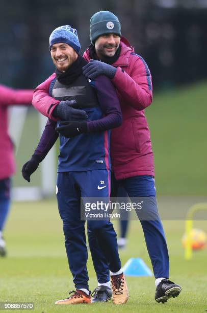 David Silva shares a joke with Pep Guardiola of Manchester City during the training session at Manchester City Football Academy on January 18 2018 in...