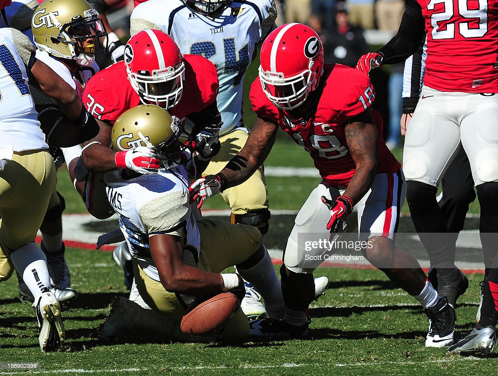 David Sims #20 of the Georgia Tech Yellow Jackets fumbles after being hit by Bacarri Rambo #18 and Shawn Williams #36 of the Georgia Bulldogs at Sanford Stadium on November 24, 2012 in Athens, Georgia.