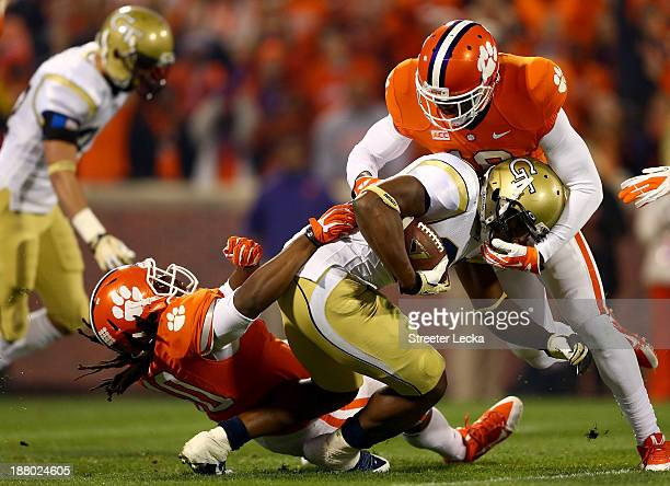 David Sims of the Georgia Tech Yellow Jackets is hit by teammates Jadar Johnson and Darrell Smith of the Clemson Tigers during their game at Clemson...