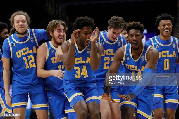 David Singleton of the UCLA Bruins and Kenneth Nwuba celebrate with teammates after defeating the Alabama Crimson Tide 88-78 in overtime in the Sweet...