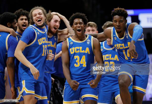 David Singleton of the UCLA Bruins celebrates with Kenneth Nwuba and Mac Etienne after defeating the Alabama Crimson Tide 88-78 in overtime in the...