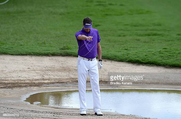 David Smail of New Zealand plays a drop after his ball lands in the water that had gathered in the bunker on the 18th hole during day two of the 2014...
