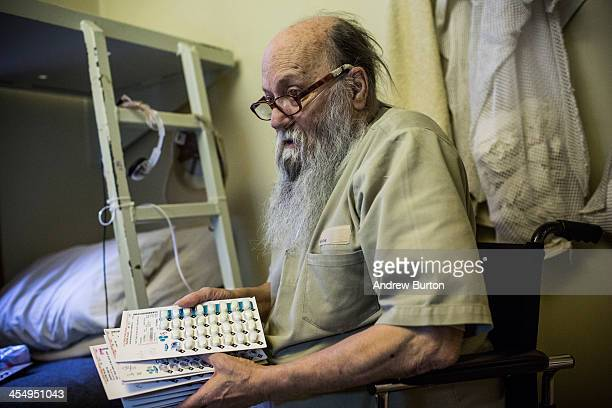 David Smith a prisoner at Rhode Island's John J Moran Medium Security Prison displays a pile of medications while watching television during free...