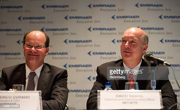 David Sokol chairman and chief executive officer of NetJets Inc right speaks while Frederico Curado president and chief executive officer of Empresa...