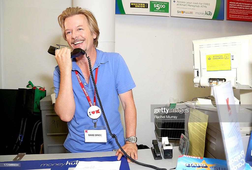 David Spade makes overhead announcements as he celebrates the upcoming release of GROWN UPS 2 by manning Kmart registers, where he shares news about the movie and the store's donation to the March of Dimes at KMart on July 3, 2013 in Los Angeles, California.