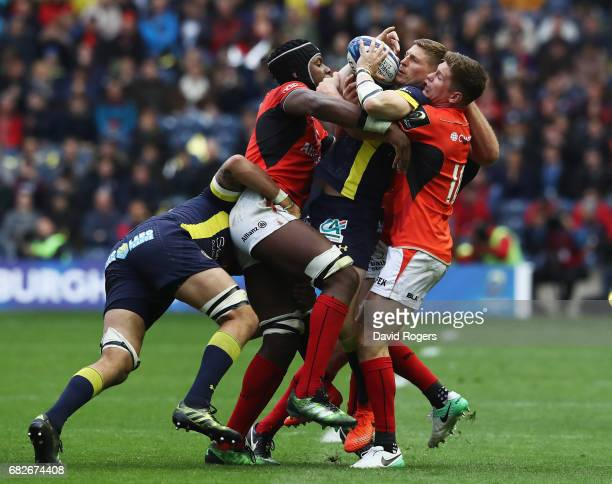 David Strettle of Clermont Auvergne is tackled by Maro Itoje and Owen Farrell of Saracens during the European Rugby Champions Cup Final between ASM...