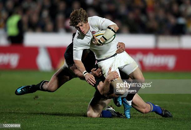 David Strettle of England is tackled by Berrick Barnes and Anthony Faingaa during the match between the Australian Barbarians and England at on June...