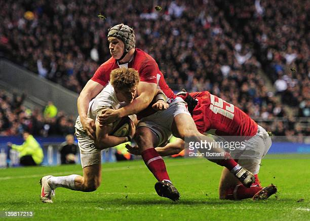 David Strettle of England Jonathan Davies and Leigh Halfpenny of Wales is tackled by as he crosses the try line but the try is not given during the...