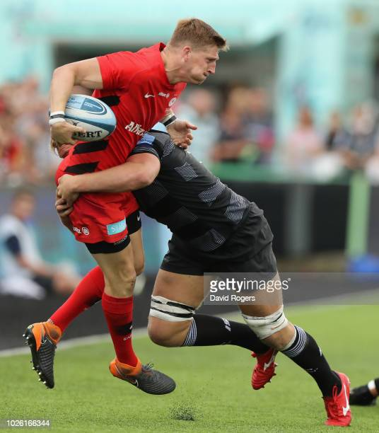 David Strettle of Saracens is tackled by Callum Chick which resulted in Strettle being replaced during the Gallagher Premiership Rugby match between...