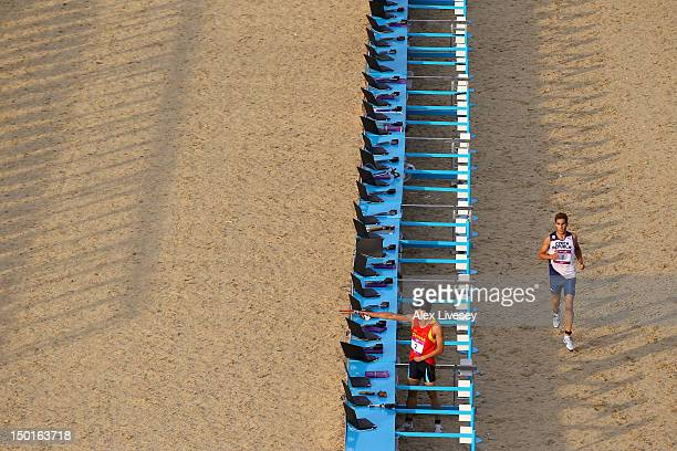 David Svoboda of Czech Republic runs after shooting whilst Zhongrong Cao of China continues shooting in the Combined Running/Shooting event in the...