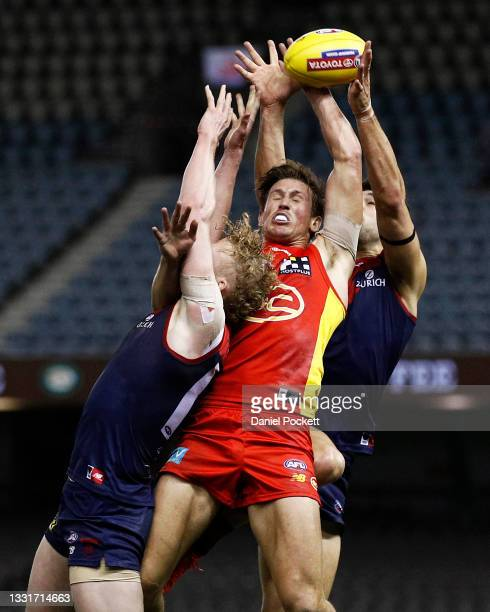 David Swallow of the Suns attempts to mark the ball against Clayton Oliver of the Demons and Christian Petracca of the Demons during the round 20 AFL...