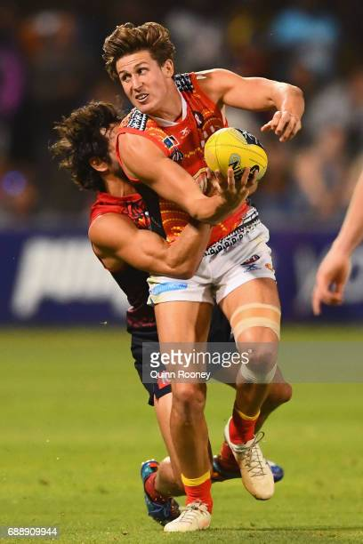 David Swallow of the Suns handballs whilst being tackled by Jeff Garlett of the Demons during the round ten AFL match between the Melbourne Demons...