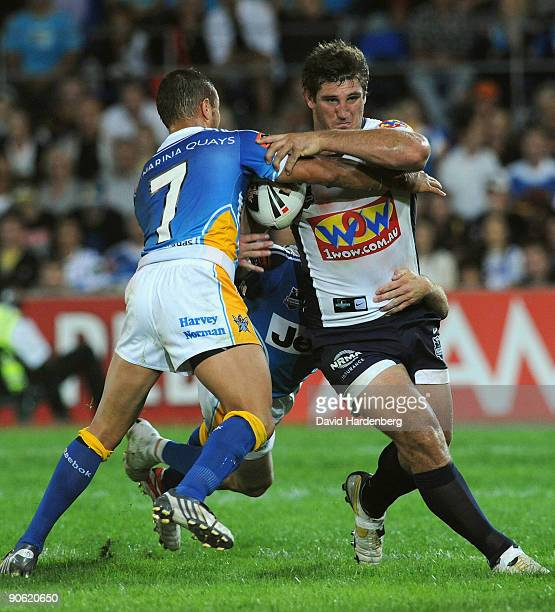 David Taylor of the Broncos is tackled by Scott Prince of the Titans during the second NRL qualifying final match between the Gold Coast Titans and...