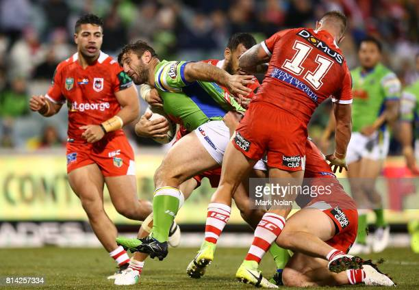 David Taylor of the Raiders is tackled during the round 19 NRL match between the Canberra Raiders and the St George Illawarra Dragons at GIO Stadium...