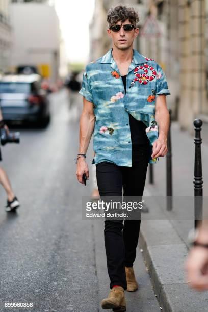 David Thielebeule wears sunglasses a flower print blue shirt black pants outside the OAMC show during Paris Fashion Week Menswear Spring/Summer 2018...