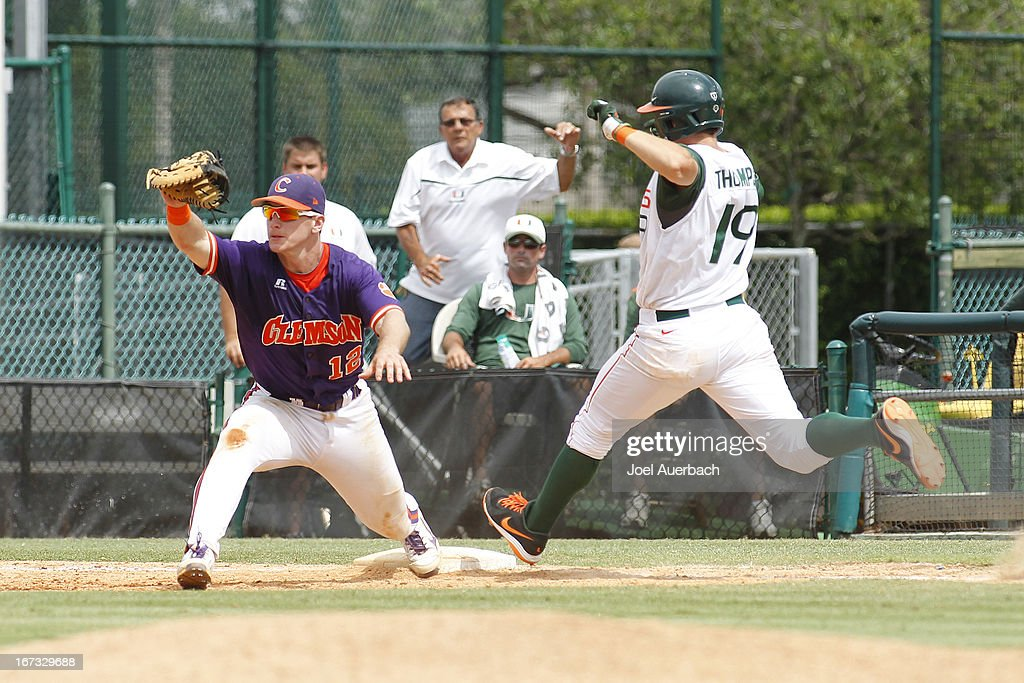 David Thompson #19 of the Miami Hurricanes reaches first base safe before the ball reaches Jon McGibbon #12 of the Clemson Tigers on April 21, 2013 at Alex Rodriguez Park at Mark Light Field in Coral Gables, Florida. Miami defeated Clemson 7-0.