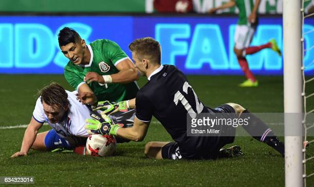 David Thor Vidarsson of Iceland tries to block a shot by Alan Pulido of Mexico as goaltender Frederik Schram of Iceland defends during their...