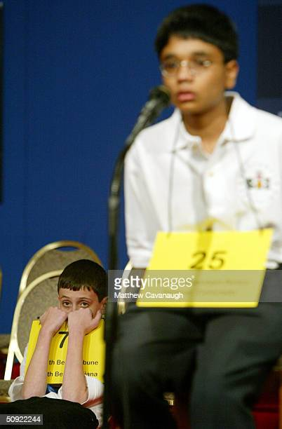 David Tidmarsh of South Bend Indiana peers over his placard as his final opponent Akshay Buddiga of Colorado Springs Colorado spells a word during...