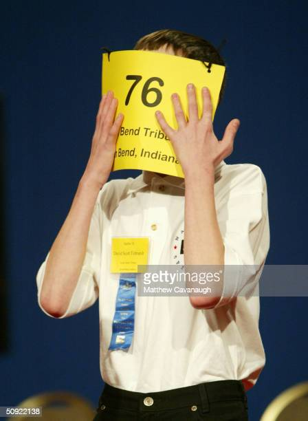 David Tidmarsh of South Bend IN covers his face with his placard after spelling the word gaminerie correctly to advance to round 15 during the...