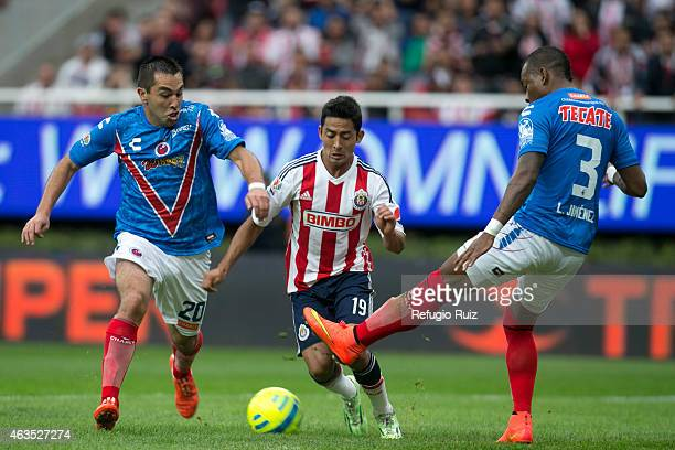 David Toledo of Chivas, fights for the ball with Fernando Meneses and Leiton Jimenez of Veracruz during a match between Chivas and Veracruz as part...