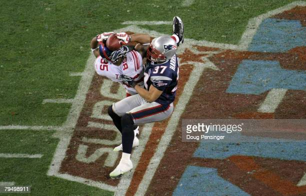 David Tyree of the New York Giants catches a 32yard pass from Eli Manning as Rodney Harrison of the New England Patriots attempts to knock it out in...