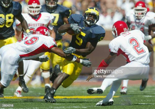 David Underwood of the Michigan Wolverines runs the ball against Will Gulley and Roland Cola of the Houston Cougars on September 6 2003 in Ann Arbor...