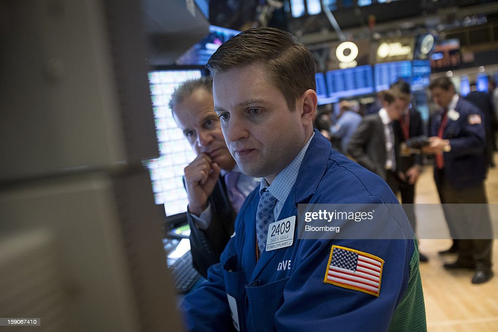 David Vadala, a trader with Virtu Financial Capital Markets LLC, right views a monitor while working on the floor of the New York Stock Exchange (NYSE) in New York, U.S., on Monday, Jan. 7, 2013. U.S. stocks fell, after the Standard & Poor's 500 Index climbed to a five-year high, as investors awaited the start of the corporate earnings season tomorrow. Photographer: Scott Eells/Bloomberg via Getty Images