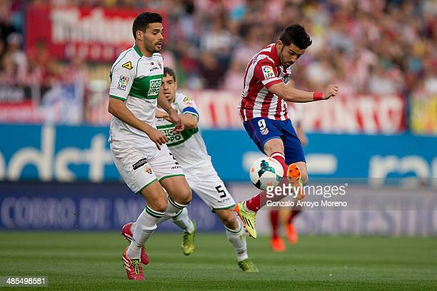 David Villa of Atletico de Madrid competes for the ball with Alberto Tomas Botia of Elche FC during the La Liga match between Club Atletico de Madrid...