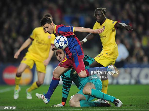 David Villa of Barcelona is tackled by Manuel Almunia and Bacary Sagna of Arsenal during the UEFA Champions League round of 16 second leg match...