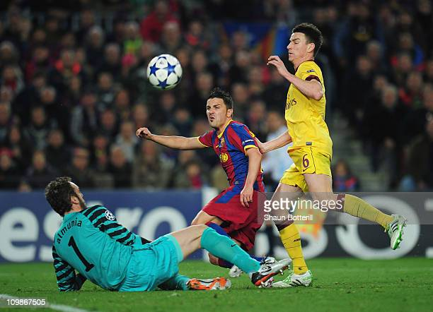 David Villa of Barcelona is tackled by Manuel Almunia and Laurent Koscielny of Arsenal during the UEFA Champions League round of 16 second leg match...