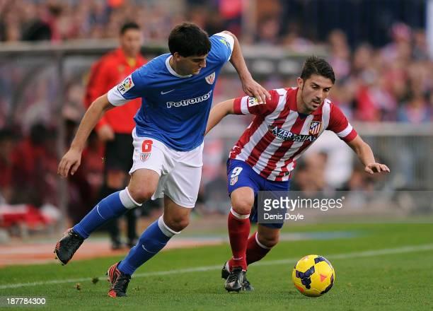 David Villa of Club Atletico de Madrid battles for the ball against Mikel San Jose of Athletic Club during the La Liga match between Club Atletico de...