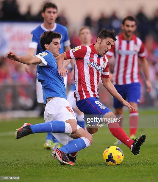 David Villa of Club Atletico de Madrid is tackled by Mikel San Jose of Athletic Club during the La Liga match between Club Atletico de Madrid and...