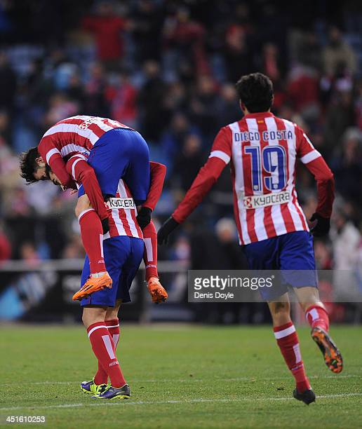 David Villa of Club Atletico de Madrid jumps onto Adrian Lopez while Diego Costa looks on after Lopez scored Atletico's 7th goal during the La Liga...