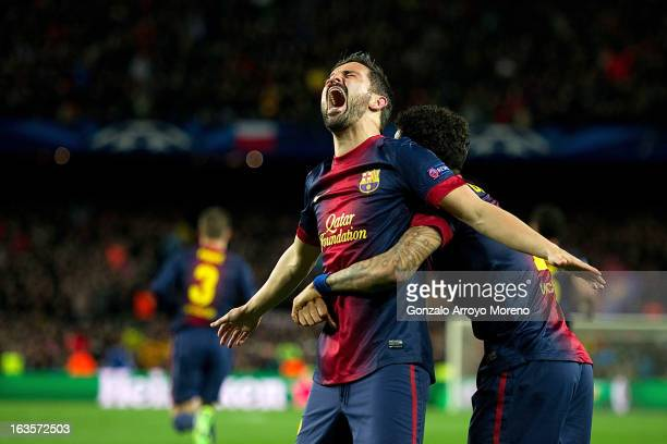 David Villa of FC Barcelona celebrates scoring their third goal with teammate Dani Alves during the UEFA Champions League Round of 16 second leg...