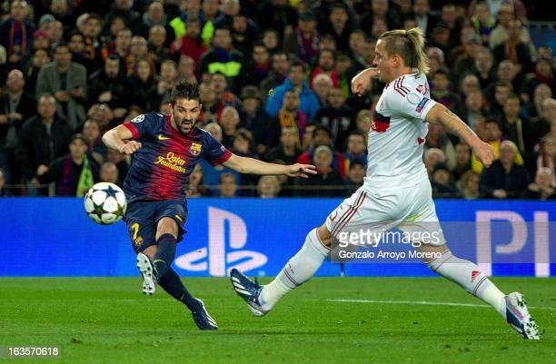 David Villa of FC Barcelona scores their third goal while Philippe Mexes of AC Milan tries to stop him during the UEFA Champions League Round of 16...