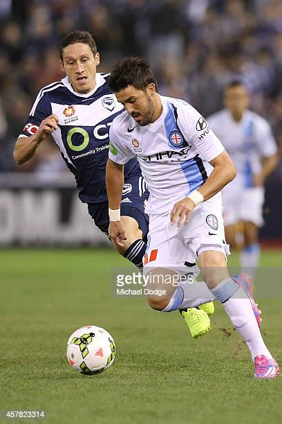 David Villa of Melbourne City runs with the ball against Mark Milligan of the Victory during the round three A-League match between the Melbourne...