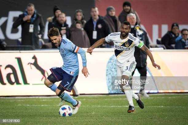 David Villa of New York City begins to go down after a hit from Ashley Cole of Los Angeles Galaxy just before Cole gets a 2nd yellow card of the...