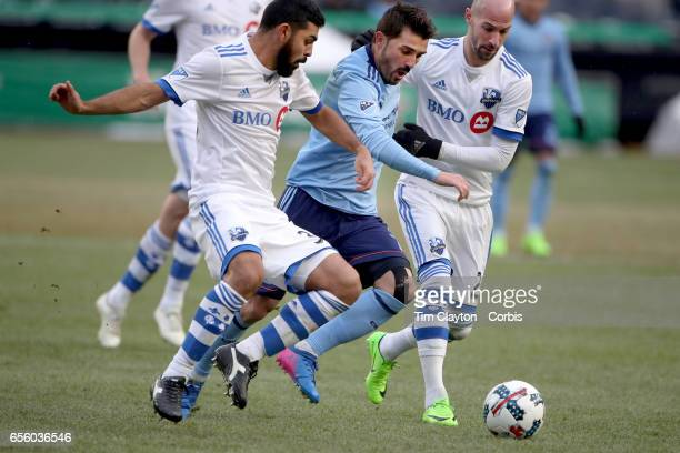 David Villa of New York City FC is challenged by Laurent Ciman of Montreal Impact and Victor Cabrera of Montreal Impact during the New York City FC...