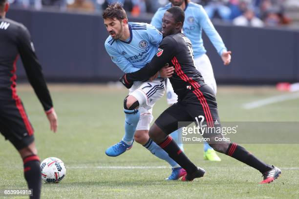 David Villa of New York City FC is challenged by Patrick Nyarko of DC United during the NYCFC Vs DC United regular season MLS game at Yankee Stadium...