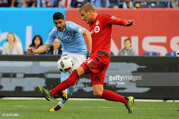 David Villa of New York City FC kicks the ball past Damien Perquis of Toronto FCat Yankee Stadium on March 13 2016 in the Bronx borough of New York...
