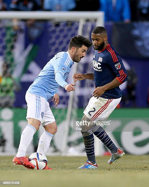 David Villa of New York City FC tries to keep the ball from Andrew Farrell of New England Revolution during the inaugural game of the New York City...