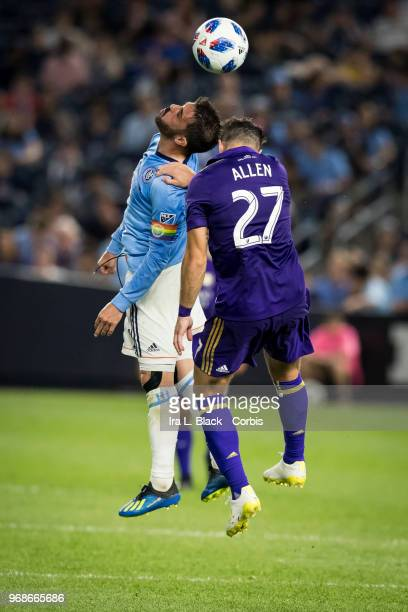 David Villa of New York City wears a rainbow Captain's arm band and goes up for the header against RJ Allen of Orlando City during the MLS the pride...