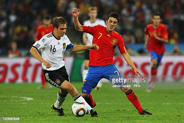 David Villa of Spain battles for the ball with Philipp Lahm of Germany during the 2010 FIFA World Cup South Africa Semi Final match between Germany...