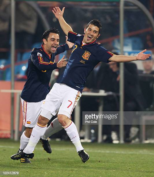David Villa of Spain celebrates scoring the opening goal with team mate Xavi Hernandez during the 2010 FIFA World Cup South Africa Group H match...