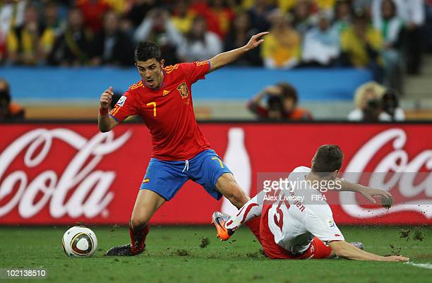 David Villa of Spain is challenged by Steve von Bergen of Switzerland during the 2010 FIFA World Cup South Africa Group H match between Spain and...