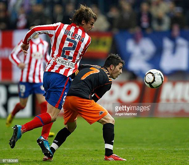 David Villa of Valencia competes for a ball with Juan Valera of Atletico Madrid during the La Liga match between Atletico Madrid and Valencia at...